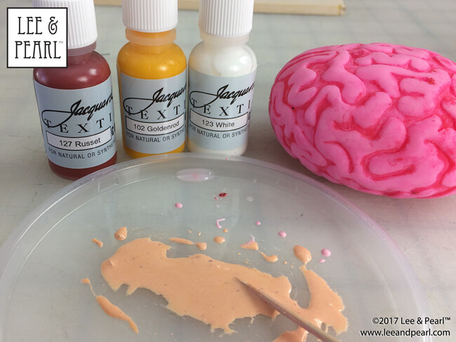 "When we found this hot pink, squishy ""brain"" squeeze toy in the check out line bins at our local craft store, we knew that this had to be our next painted project for 18 inch dolls — and the star prop of our Halloween 2017 Mad Scientist Laboratory pictorial. Join us as we walk you step-by-step through the process of turning an inexpensive plastic toy into a one-of-a-kind doll treasure!"